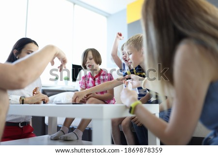 Team of children play against team of adults in board games with cards in room on table. Photo stock ©