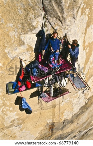 Team of climbers bivouacked in their portaledges on the side of a bigwall.