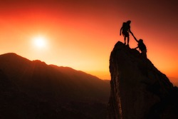 Team of climbers help to conquer the summit in teamwork in a fantastic mountain landscape at sunset