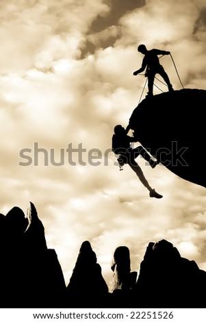 Team of climbers reaching the summit of a rock pinnacle in The Sierra Nevada Mountains, California.