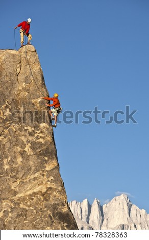 Team of climbers struggle to reach the summit of an challenging rock pinnacle.