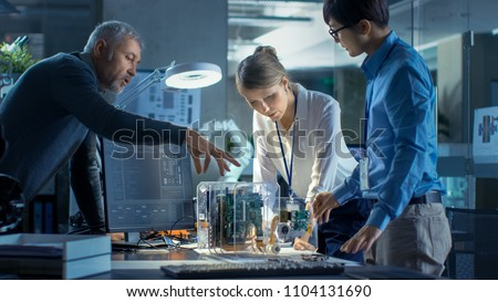 Team of Computer Engineers Lean on the Desk and Choose Printed Circuit Boards to Work with, Computer Shows Programming in Progress. In Background Technologically Advanced Scientific Research Center.