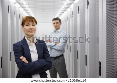 Team of computer technicians looking at camera in large data center #210586114
