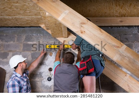 Team of Construction Workers Building Wooden Staircase Frame in Unfinished Basement of New Home, Checking Levels for Accuracy and Quality Control