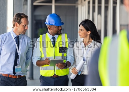 Team of construction workers discussing project details with executive supervisor. Group of architects and civil engineers inspecting construction site. Structural engineer and architect discussing.