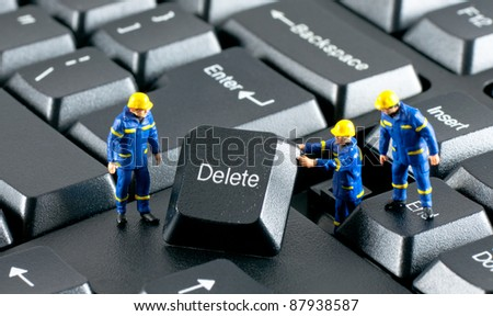 Team of construction workers working with DELETE button on a computer keyboard