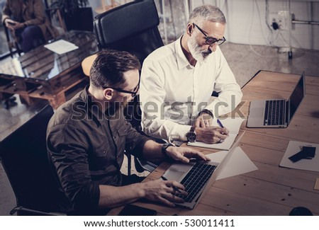 Team of coworkers making great work discussion in modern office.Adult bearded man writing new ideas in notebook.Young man using laptop.Business people meeting concept.Horizontal, blurred