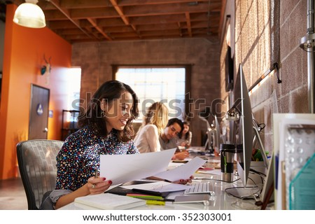 Team Of Designers Working At Desks In Modern Office