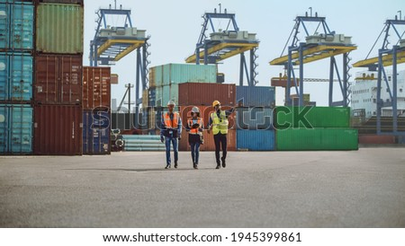 Team of Diverse Industrial Engineers, Safety Supervisors and Foremen in Hard Hats and Safety Vests Walking in Shipping Cargo Container Terminal Depot. Colleagues Talk About Logistics Operations. Сток-фото ©