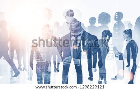 Team of diverse managers working with gadgets and documents over foggy cityscape background. Concept of teamwork. Toned image double exposure
