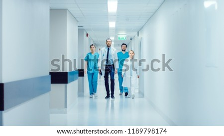 Team of Doctors, Surgeons and Nurses Walk Through Busy Hospital Hallway, They Talk about Patients, Forthcoming Surgeries and Saving Lives. Clean Modern Hospital with Professional Staff. Сток-фото ©