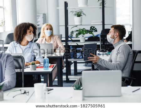 Team of employees working on project and social distancing during outbreak. Millennial male manager in protective mask talk to european and african american women at work desks with laptops