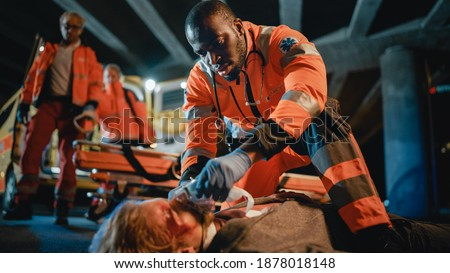 Team of EMS Paramedics Provide Medical Help to an Injured Young Man. Doctor in Gloves Attaches Ventilation Mask on a Patient. Emergency Care Assistants Arrived in an Ambulance Vehicle at Night. Сток-фото ©