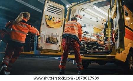 Team of EMS Paramedics Quickly Take Out a Stretcher from Ambulance Vehicle and Help an Injured Person. Emergency Care Assistants Arrived on the Scene of a Traffic Accident on a Street at Night.
