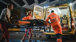 Team of EMS Paramedics React Quick to Provide Medical Help to Injured Patient and Get Him in Ambulance on a Stretcher. Emergency Care Assistants Arrived on the Scene of a Traffic Accident on a Street. Blurry