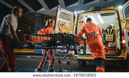 Team of EMS Paramedics React Quick to Provide Medical Help to Injured Patient and Get Him in Ambulance on a Stretcher. Emergency Care Assistants Arrived on the Scene of a Traffic Accident on a Street. Blurry Сток-фото ©