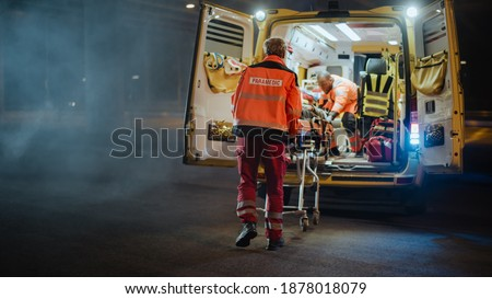 Team of EMS Paramedics React Quick to Provide Medical Help to Injured Patient and Get Him in Ambulance on a Stretcher. Emergency Care Assistants Arrived on the Scene of a Traffic Accident on a Street. Blur