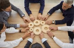 Team of entrepreneurs collaborate and develop effective business system. Group of senior and young business people join gearwheels as metaphor for good cooperation and teamwork, high angle, from above