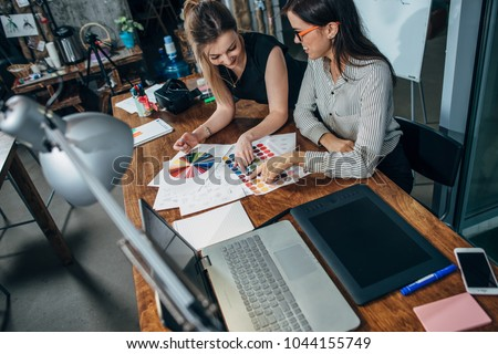 Team of female interior designer drawing a new project using graphic tablet, laptop and color palette sitting at desk in modern studio