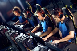 Team of focused professional cybersport gamers wearing headphones playing online video games while sitting in gaming club or in internet cafe