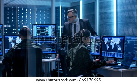 Team of Government Agents Tracking Fugitive with Boss's Survillance in Big Monitoring Room Full of Computers with Animated Screens.