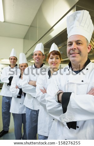 Team of happy chefs smiling at the camera in a kitchen wearing uniforms