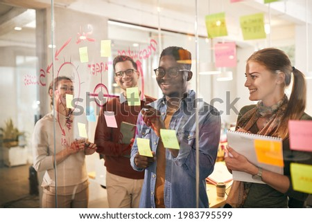 team of happy freelancers brainstorming in front of mind map o glass wall during business project in the office. Focus is on African American man. The view is through the glass. Foto stock ©