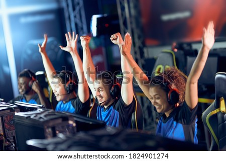 Team of happy professional cyber sport gamers celebrating success while participating in eSports tournament, playing online video games