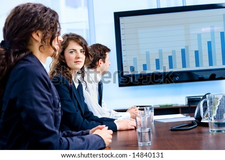 Team of happy young businesspeople having meeting in boardroom at office in front of a huge plasma TV screen, indoor, smiling. - stock photo