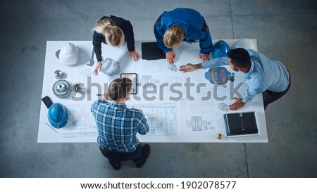 Team of Industrial Engineers Lean on Office Table, Analyze Machinery Blueprints, Architectural Problem Solving, Consult Project on Tablet Computer, Inspect Metal Component. Flat Lay Top Down View Сток-фото ©
