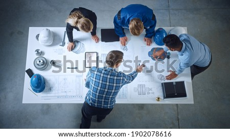 Team of Industrial Engineers Lean on Office Table, Analyze Machinery Blueprints, Architectural Problem Solving, Consult Project on Tablet Computer, Inspect Metal Component. Flat Lay Top Down View Stockfoto ©