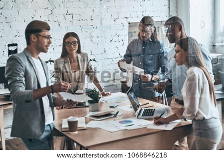 Team of innovators. Group of young modern people in smart casual wear discussing business while standing behind the glass wall in the creative office