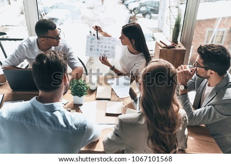 Team of innovators. Top view of young modern people in smart casual wear discussing business while working in the creative office