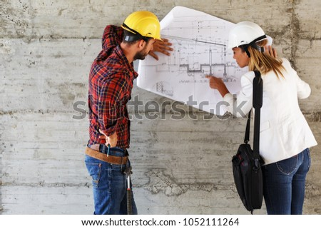 Shutterstock puzzlepix team of inspectors and architects discuss about blueprints on construction site malvernweather Images