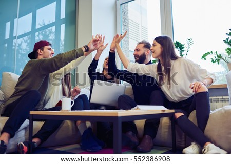 Team of male and female freelancers celebration finishing work on creation successful startup strategy using digital devices and internet connection giving high five and feeling exciting in workshop #552386908