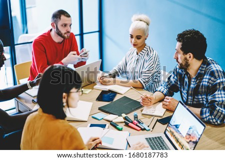 Team of male and female multiracial designers sitting at table together during working brainstorming session using gadgets for analyzing and research, group of smart young 20s students prepare project