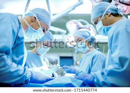 Team of male and female surgeons operating patient in operating room at hospital. Horizontal shot.
