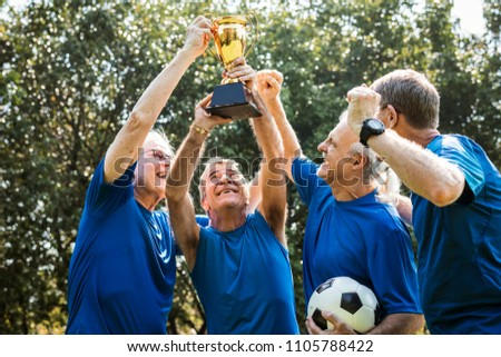 Team of mature football players winning the cup #1105788422
