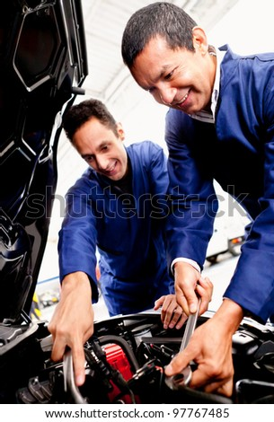 Team of mechanics fixing a car at the garage - stock photo