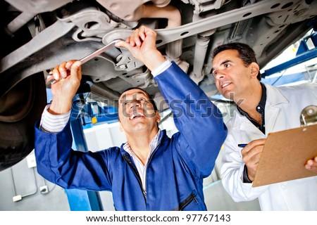 Team of mechanics working under a car at the garage