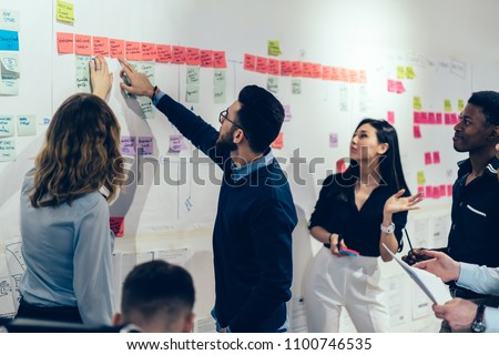 Team of multicultural young people pointing on wall with glued colorful paper notes with foreign words during productive lesson.Diverse group of male and female employees in formal wear using stickers #1100746535