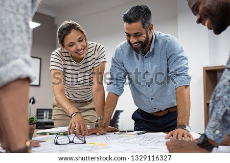 Team of multiethnic architects working on construction plans in meeting room. Engineers discussing on project in office. Mature businessman and woman standing around table working on blueprint.