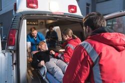 team of paramedics moving wounded mature man into ambulance