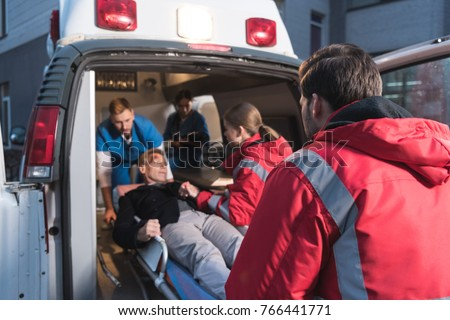 team of paramedics moving wounded mature man into ambulance