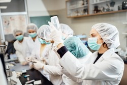 Team of pharmacists developing parenteral antibody antivirus.Pharmaceutical development of a new vaccine.Parenteral antibiotic safety control test examination in the cleanroom.Virus epidemic concept