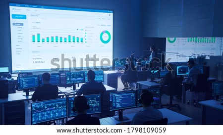 Team of Professional Big Data Business Traders Work on Desktops with Screens Showing Charts, Graphs, Infographics, Technical Neural Data and Statistics. Low Key Control and Monitoring Room.