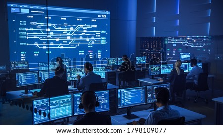 Team of Professional Computer Data Science Engineers Work on Desktops with Screens Showing Charts, Graphs, Infographics, Technical Neural Data and Statistics. Low Key Control and Monitoring Room. Сток-фото ©