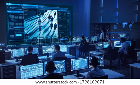 Team of Professional Cyber Security Data Science Engineers Work on Surveillance Tracking Shot of People Walking on City Streets. Big Dark Control and Monitoring Room with Computer Displays. ストックフォト ©