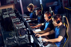 Team of professional cybersport gamers wearing headphones participating in eSport tournament while sitting in gaming club or in internet cafe