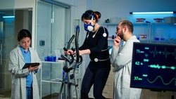 Team of professional doctors measuring health conditions of woman athlete in science sport laboratory. Physician using tablet controling EKG data, muscle endurance, heart rate psychological resistance